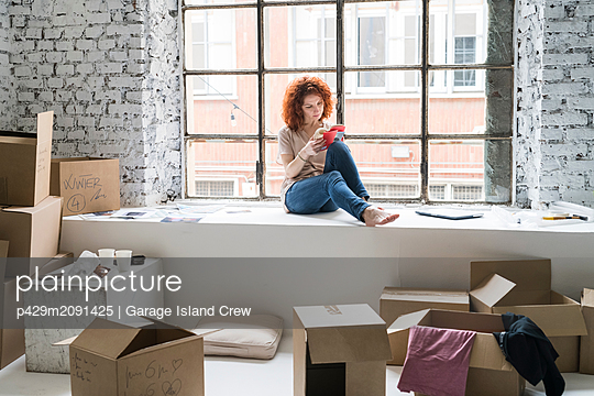 Mid adult woman moving into industrial style apartment, sitting on window ledge looking at book - p429m2091425 by Garage Island Crew