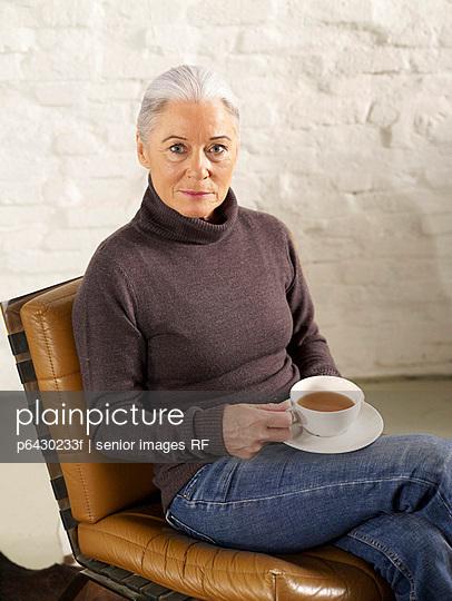 Aeltere Frau trinkt einen Tee  - p6430233f von senior images RF