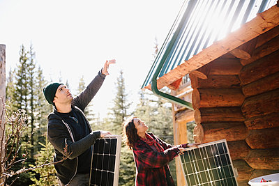 Couple installing solar panels on cabin - p1192m2093971 by Hero Images