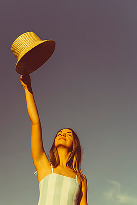 Junge Frau hält Hut in der Hand - p432m2260423 von mia takahara