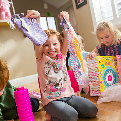 Caucasian girl showing gifts at party - p555m1304996 by Mike Kemp