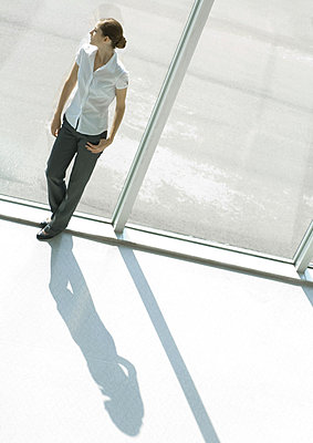 Woman standing by window - p6239759f by Milena Boniek