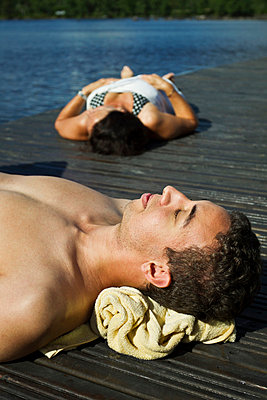 Young man and woman sunbathing on the pier. (Ung man och kvinna solar på brygga.) - p847m673080 by Anna Molander