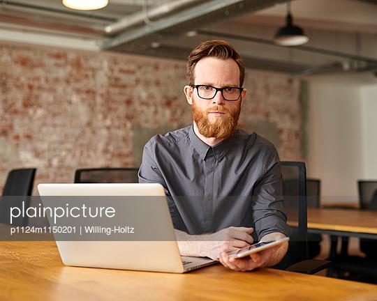 Junger Mann mit Tablet und Laptop am Arbeitsplatz - p1124m1150201 von Willing-Holtz