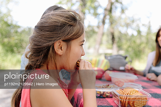 Girl eating food at family picnic in park - p1192m2129942 by Hero Images