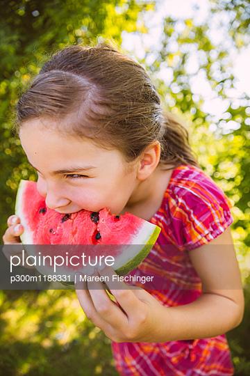 Girl eating slice of watermelon in garden - p300m1188331 by Mareen Fischinger
