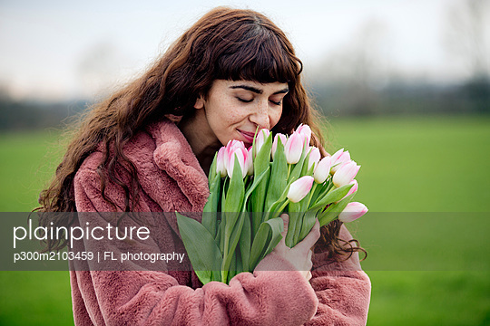 Young woman with bouquet of tulips and pink coat - p300m2103459 by FL photography