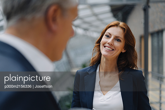 Portrait of smiling businesswoman talking to businessman in office - p300m2156336 by Joseffson