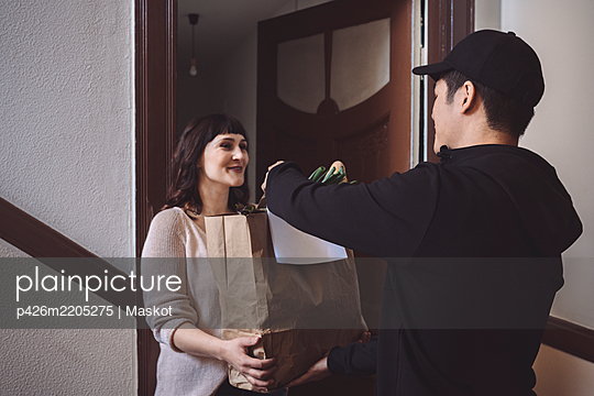 Smiling customer talking to delivery man while holding vegetable bag at doorstep - p426m2205275 by Maskot