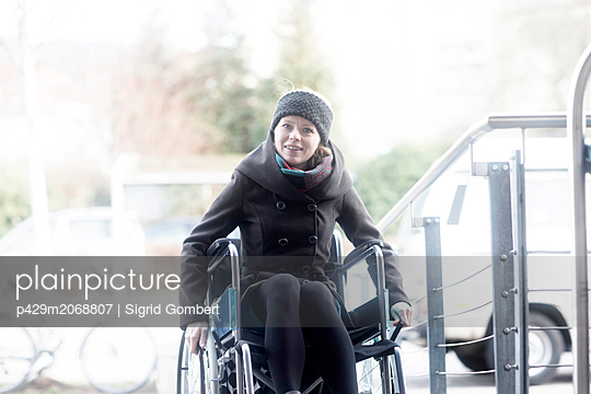 Woman in wheelchair moving up ramp - p429m2068807 by Sigrid Gombert