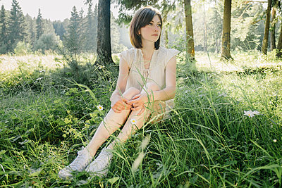 Full length of thoughtful young woman looking away while sitting on grassy field in forest - p1166m2025105 by Cavan Social