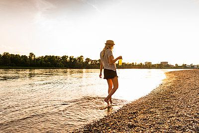 Young woman walking barefoot on riverside in the evening - p300m2005343 von Uwe Umstätter