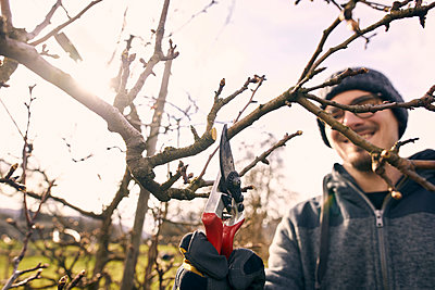 Smiling male farmer with pruning shears cutting bare tree branch - p300m2277601 by Sebastian Dorn