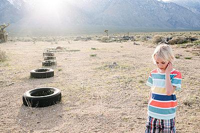 Boy exploring beside row of tyres, Olancha, California, US - p924m2127294 by Viara Mileva