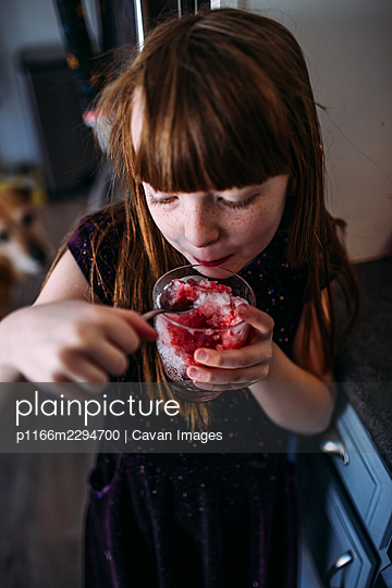 Vertical portrait of young girl eating a snow cone inside - p1166m2294700 by Cavan Images