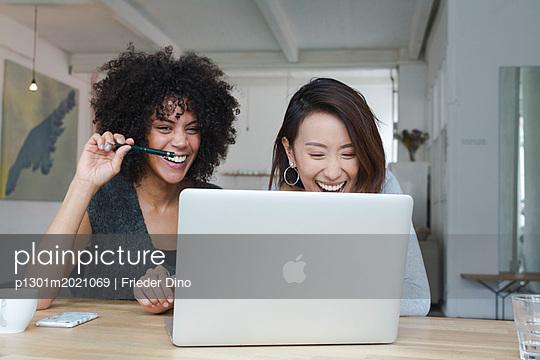 Zwei junge Kolleginnen lächelnd vor Laptop  - p1301m2021069 von Delia Baum