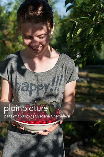 Teenager holding a plate with sweet cherries - p1412m1584257 by Svetlana Shemeleva