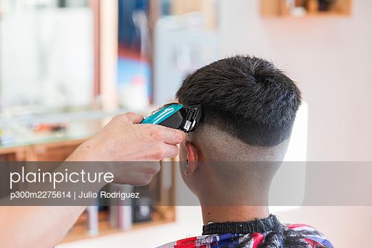 Hairdresser cutting a teenager boy hair with a machine, Matalascañas, Spain - p300m2275614 von Julio Rodriguez