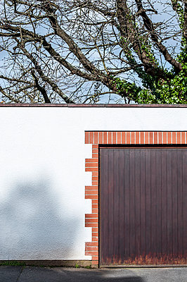 Garage door surrounded by red brickwork on a white wall with tree behind - p1047m953668 by Sally Mundy