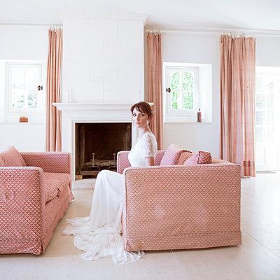 Bride in wedding dress sits in living room  - p1105m2126405 by Virginie Plauchut