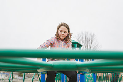 Low angle view of girl climbing on jungle gym against clear sky at playground - p1166m1423344 by Cavan Images