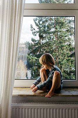 Junge sitzt auf Fensterbank - p118m2231825 von Daniel Sadrowski