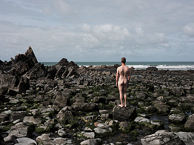 Naked man is standing on a stone on a rugged coast - p1383m2026505 by Wolfgang Steiner