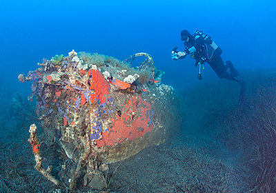 France, Corsica, Scuba diver swimming by demolished cockpit of sunken wreck of P-47 Thunderbolt plane - p300m2154107 by Christian Zappel