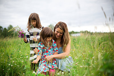 Mother with daughters on meadow - p312m2051619 by Matilda Holmqvist