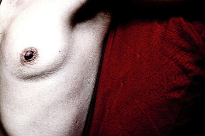 Naked woman's breast against a red cloth - p3314097 by Anna Fabroni