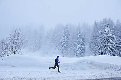 Distant view of male runner running in deep snow, Gstaad, Switzerland - p429m1417993 by Jakob Helbig