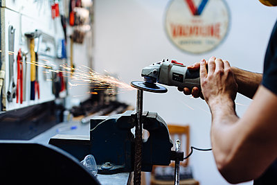 Young man using angle grinder on metal in workshop, cropped - p429m2202351 by Sofie Delauw