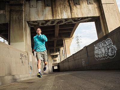 Caucasian man running in urban tunnel - p555m1420158 by Erik Isakson