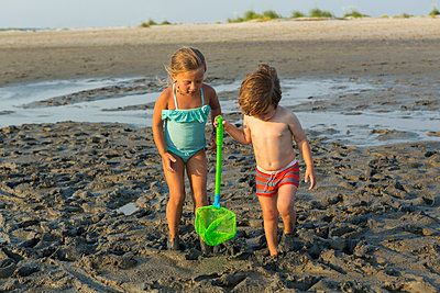 Caucasian brother and sister carrying net on beach - p555m1522788 by Marc Romanelli
