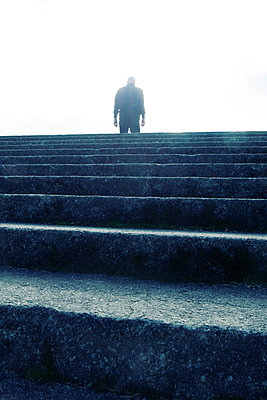 Rearview man standing at top of stone steps - p597m1488670 by Tim Robinson