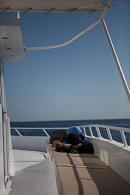 Junger Mann entspannt sich an Deck eines Bootes - p772m2179757 von bellabellinsky