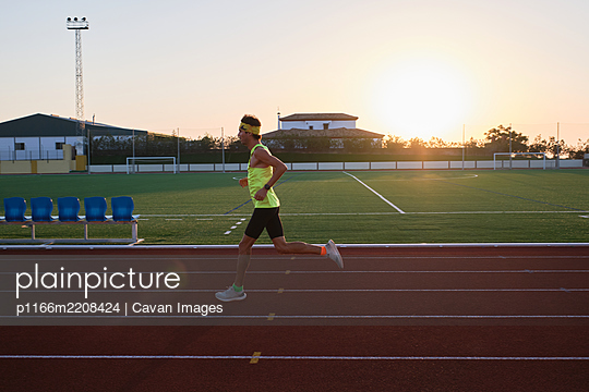 young man trains running on new and red tracks - p1166m2208424 by Cavan Images