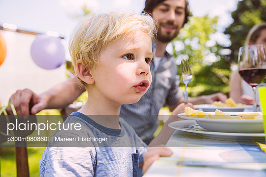 Boy eating pasta with family at garden table - p300m980860f by Mareen Fischinger