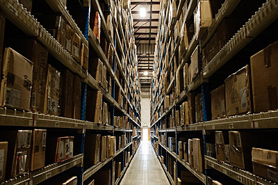 View down an aisle of racks holding cardboard boxes of product on pallets  in a large distribution warehouse - p1100m1575499 by Mint Images