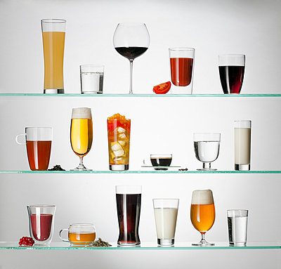 A collection of various types of drinking glasses filled with a variety of beverages - p301m744182f by Larry Washburn