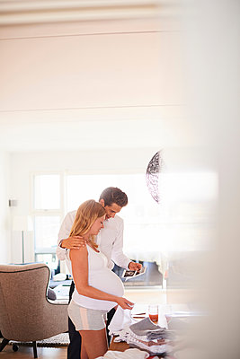 Pregnant couple looking at ultrasound pictures in living room - p429m1513746 by Jakob Helbig