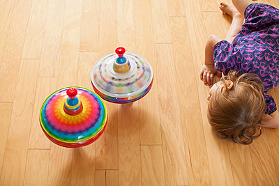 Girl playing with spinning tops - p429m817350 by Angela Bird