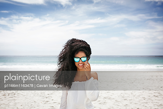 Portrait of happy woman standing on beach against sky - p1166m1163478 by Cavan Images