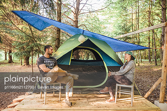 Couple laughs and talks outside of tent campsite in upstate New York - p1166m2112700 by Cavan Images
