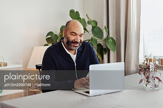 Smiling man using laptop at home - p312m2299748 by Plattform