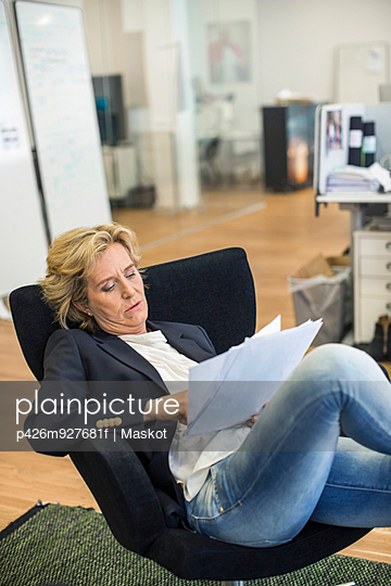 Relaxed businesswoman reading documents while sitting on chair in office