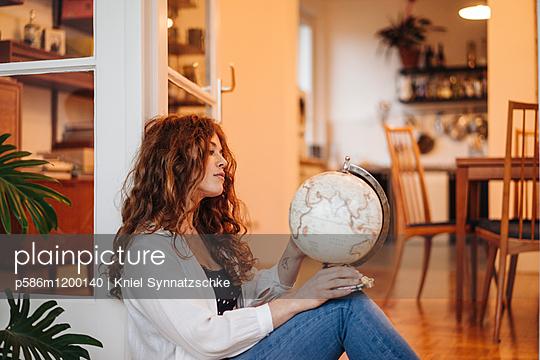 Junge Frau blickt auf einen Globus - p586m1200140 von Kniel Synnatzschke