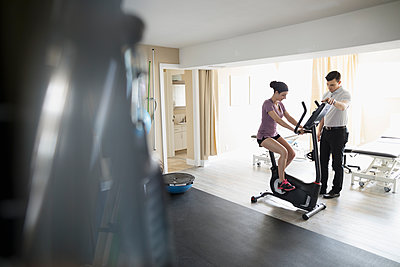 Male physiotherapist guiding female client exercising on exercise bicycle in clinic gym - p1192m1447352 by Hero Images