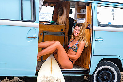 Portrait of happy young woman with surfboard in van - p300m1505633 by Simona Pilolla