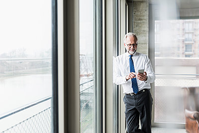 Smiling mature businessman standing at the window using cell phone - p300m1563024 by Uwe Umstätter